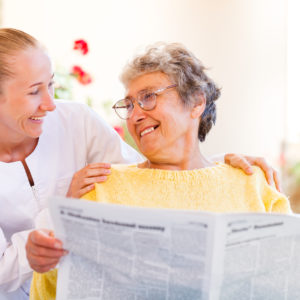 Aide_Smiling_Woman_Reading_Newspaper